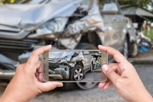 Person taking picture with phone of Car Crash